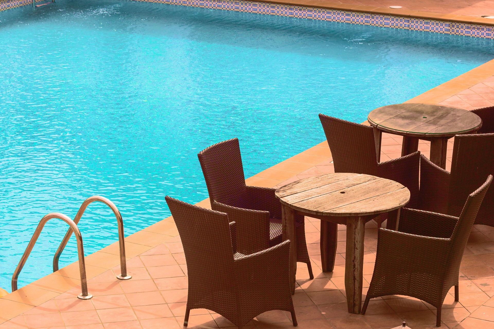 chairs and tables near pool